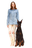 Röd flicka i jeans med den stora hunden Arkivbild