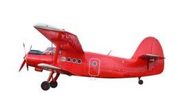 Röd flygplanbiplan med pistongmotorn Arkivbild