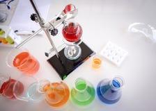 Röd flytande i exponeringsglas som testar flaskan på kuggen arkivfoton