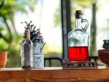 Röd flytande i glasflaskor på trätabellen på kafét, dricka för dryck royaltyfria foton