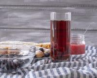 Röd fruktsaft i ett exponeringsglas bredvid en bunke av kakor och en krus av driftstopp, på en grå bakgrund arkivbilder