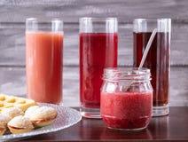 Röd fruktsaft i ett exponeringsglas bredvid en bunke av kakor och en liten krus av driftstopp royaltyfria bilder