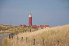 Röd fyr, lilla hus på Texel Arkivbild