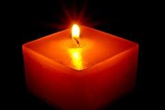 Röd fyrsidig stearinljus i mörkret. Arkivbilder