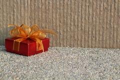 Röd gåva med det guld- bandet Royaltyfri Foto