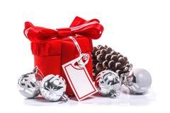 Röd gåva med pilbågen och julbollar. arkivfoton