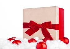 Röd gåvaask för jul med leksaker och snö Royaltyfri Foto