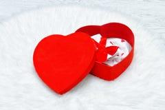 Röd gåvaask i formen av hjärta Underkläder och stearinljus arkivbild