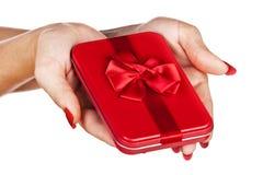 Röd gåvaask i kvinnas händer royaltyfria bilder