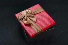 Röd gåvaask med den bruna pilbågen på mörker Royaltyfria Bilder