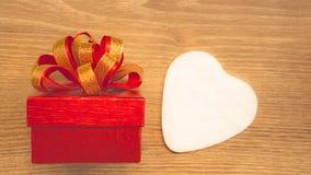 Röd gåvaask med det guld- bandet och vitt hjärtapapperssnitt för valentindaggåva på brun träbakgrund arkivfoto