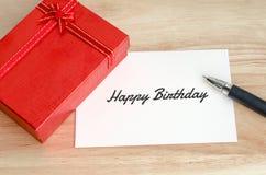 Röd gåvaask med det tomma kortet och penna på trätabellen royaltyfri fotografi