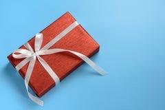Röd gåvaask med det vita bandet på blå bakgrund Fotografering för Bildbyråer