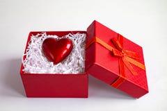 Röd gåvaask med hjärta vid på vit bakgrund royaltyfri fotografi