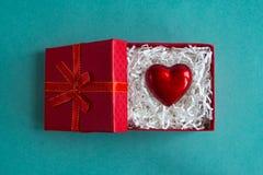 Röd gåvaask med hjärta vid valentin dag på blå bakgrund begrepp som ger hjärtaförälskelse royaltyfria bilder