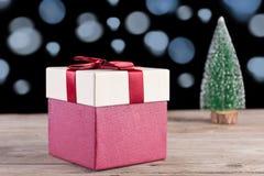 Röd gåvaask med pilbågen på det retro träskrivbordet och julgranen arkivfoton