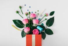 Röd gåvaask med rosor, partikonfettier, banderoller, noisemakers, Royaltyfria Bilder