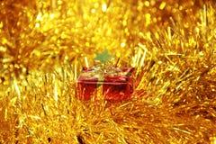 Röd gåvaask på guld- fluffiga garneringar Fotografering för Bildbyråer