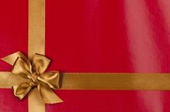 Röd gåvabakgrund med guldbandet Arkivbild