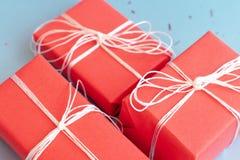 Röd gåvaboxesclose upp på blå bakgrund arkivbilder