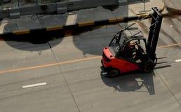 Röd gaffeltruck på fabriksvägen royaltyfri foto
