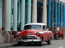RÖD GAMMAL BIL OCH RÖD TAXI, CIENFUEGOS, KUBA Arkivbild