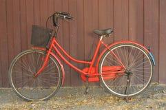 Röd gammal cykel hemma. Arkivbilder