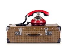 Röd gammal telefon och resväska arkivbilder