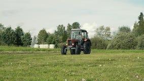 Röd gammal traktor i gårdsplanen som kör in mot arkivfilmer