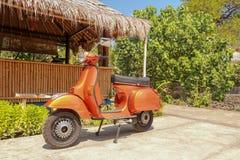 Röd gammalmodig sparkcykelmoped - indonesisk traditionell väg av trans. på en tropisk ö Orange tappningvespa royaltyfri bild