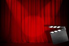 Röd gardin för teater med det tomma clapperbrädet Arkivfoto