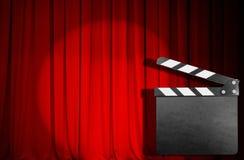 Röd gardin med den tomma filmclapperen Arkivfoto