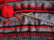 Röd garnboll och stuckit ullplagg Fotografering för Bildbyråer