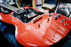 Röd gitarr i underhåll Royaltyfri Fotografi