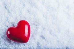 Röd glansig hjärta på en frostig vit snöbakgrund Förälskelse- och St-valentinbegrepp Royaltyfri Bild