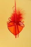 Röd glass hjärta på guling Arkivbild