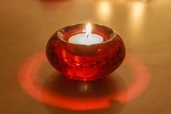 Röd Glass stearinljushållare med den vita stearinljuset Fotografering för Bildbyråer
