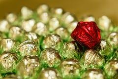 Röd godis på gröna choklader Arkivbilder