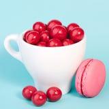 Röd godischokladboll i en kopp med makron Arkivfoton