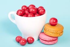 Röd godischokladboll i en kopp med makron Royaltyfria Bilder