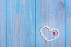 Röd godishjärta som lägger på vit, målade lantlig träbakgrund Royaltyfri Fotografi