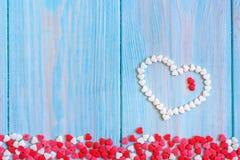 Röd godishjärta som lägger på vit, målade lantlig träbakgrund Royaltyfri Bild
