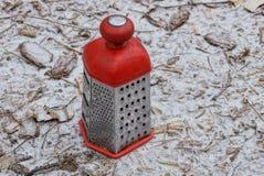 Röd-grå färger ett stort rivjärn står på jordningen i snön arkivbild