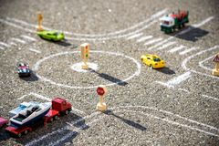 R?d gr?n bl? f?rg f?r leksakbilar p? v?gen chalked p? svart asfalt Sv?rt begrepp f?r trafikregler arkivbild