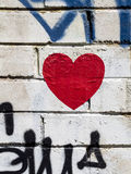 Röd grafittihjärta på den vita väggen Arkivbild