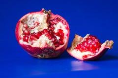 Röd granatröttfrukt med frö och skivor på blå bakgrund Royaltyfri Foto