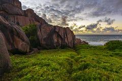 Röd granit vaggar i soluppgången på ladigue på Seychellernaen 1 Royaltyfria Bilder