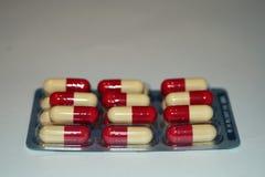 Röd gul kapsel för medicinpreventivpillerar Arkivbilder
