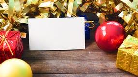 Röd guld- juldekor och tomt pappers- kort på trätabellen Garnering för nytt år på lantlig timmer Royaltyfria Bilder