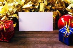 Röd guld- juldekor och tomt pappers- kort på trätabellen Julkortmodell Mall för tappningjulbaner Arkivbild